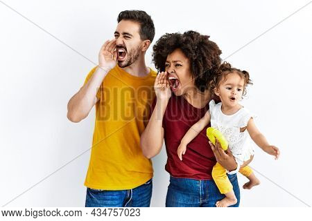 Interracial young family of black mother and hispanic father with daughter shouting and screaming loud to side with hand on mouth. communication concept.