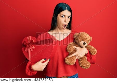 Young hispanic woman holding valentine gift in shock face, looking skeptical and sarcastic, surprised with open mouth
