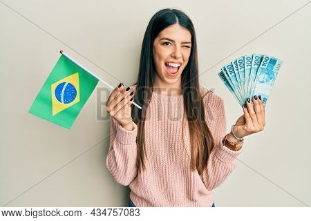 Young hispanic woman holding brazil flag and real banknotes winking looking at the camera with sexy expression, cheerful and happy face.