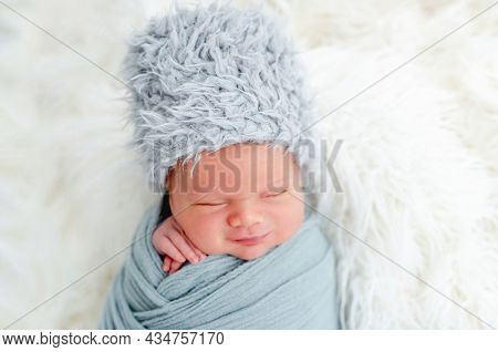 Portrait of newborn baby boy swaddled in light blue fabric and wearing furry hat sleeping in studio. Adorable infant child napping