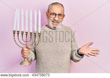 Handsome senior man with beard holding menorah hanukkah jewish candle celebrating achievement with happy smile and winner expression with raised hand