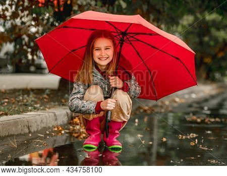 Preteen girl wearing rubber boots sitting under umbrella at autumn at street in rainy day. Pretty female kid in gumboots outdoors