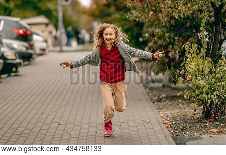 Preteen girl wearing rubber boots running at autumn at street. and smiling Pretty female kid in gumboots outdoors