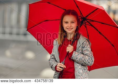 Preteen girl with umbrella standing under rain at autumn, looking at camera and smiling. Pretty kid portrait outdoors