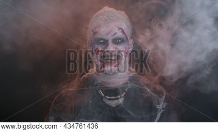 Sinister Smiling Man With Horrible Scary Halloween Zombie Makeup In Costume Making Faces, Looking Om