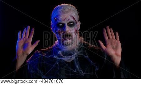 Surrender. Sinister Man In Costume Of Halloween Crazy Zombie With Bloody Wounded Scars Face Scared B