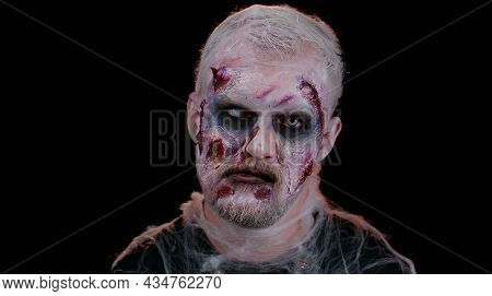 Frightening Man With Halloween Zombie Bloody Wounded Makeup, Trying To Scare, Face Expressions. Horr