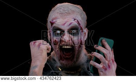 Happy Excited Sinister Man In Carnival Costume Of Halloween Crazy Zombie Looking Smartphone Display
