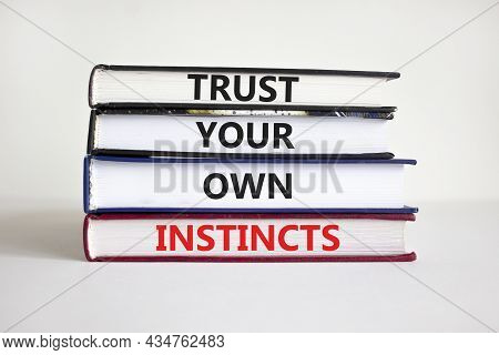 Trust Your Own Instincts Symbol. Books With Words 'trust Your Own Instincts'. Beautiful White Backgr