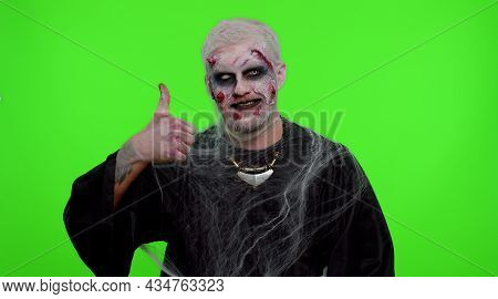 Sinister Man With Scary Halloween Zombie Makeup In Costume Raises Thumbs Up Agrees With Something Or