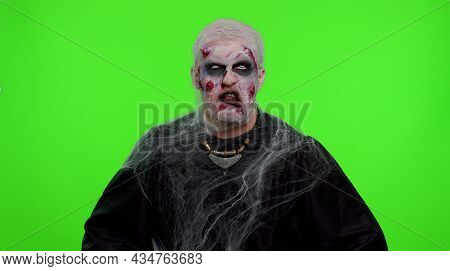 Sinister Man With Horrible Scary Halloween Zombie Makeup Making Playful Silly Facial Expressions And