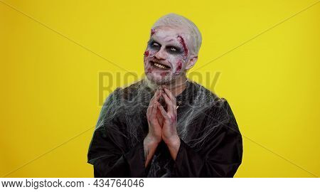 Sneaky Cunning Zombie Man With Makeup With Wounds Scars With Tricky Face Gesticulating And Scheming
