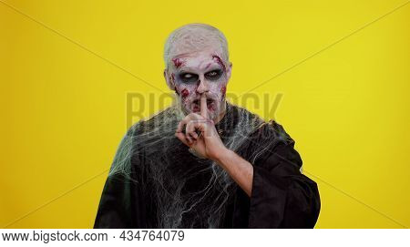 Shh Be Quiet. Sinister Man With Horrible Scary Halloween Zombie Makeup In Costume Presses Index Fing