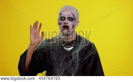 Creepy Scary Man With Bloody Scars Face, Halloween Zombie Make-up. Scary Wounded Undead Guy Waves Ha