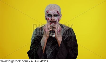 Upset Disappointed Zombie Man With Makeup With Wounds Scars Wipes Tears And Cries From Despair, Bein