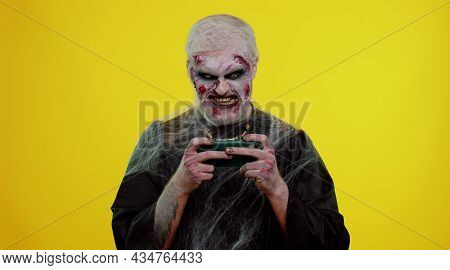 Sinister Man With Horrible Scary Halloween Zombie Makeup Enthusiastically Playing Racing Drive Video