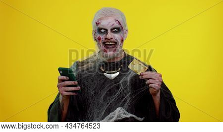 Sinister Man With Horrible Scary Halloween Zombie Make-up Using Credit Bank Card And Mobile Phone, T