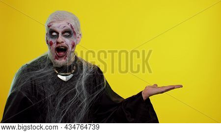 Zombie Man With Makeup With Fake Wounds Scars Showing Thumbs Up And Pointing Empty Place, Advertisin