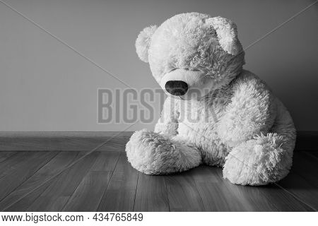 Sad Teddy Bear Sitting Alone On The Floor Loneliness And Child Abuse Concept. Black And White Image.