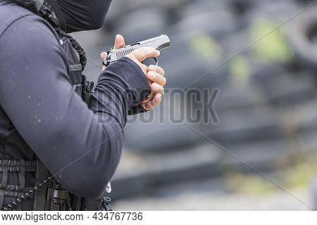Policeman Firing A Gun. Shooting Weapon. A Man Holds And Fires A Gun. A Black Pistol In Hand, Cartri