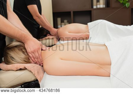 Masseur Doing Neck Massage To Young Woman Near Colleague And Blurred Man In Spa Center