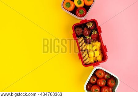 School Lunch Boxes For Storing Food And A Quick Lunch With Vegetables And Fruits On Colored Backgrou