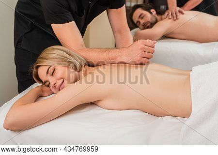 Masseur Doing Massage To Smiling Woman Near Blurred Man In Spa Center