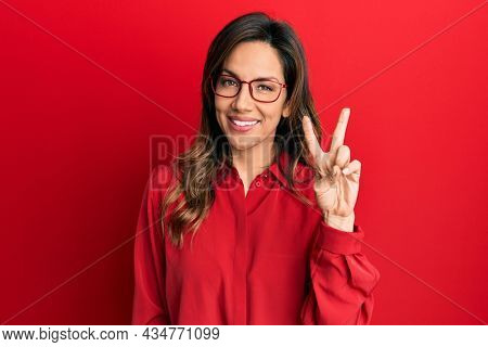 Young latin woman wearing casual clothes and glasses showing and pointing up with fingers number two while smiling confident and happy.
