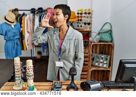 Young hispanic woman with short hair working as manager at retail boutique shouting and screaming loud to side with hand on mouth. communication concept.