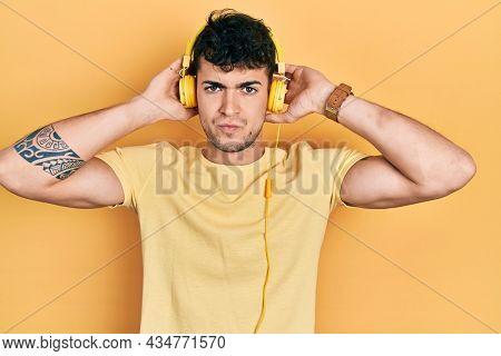 Young hispanic man listening to music using headphones skeptic and nervous, frowning upset because of problem. negative person.