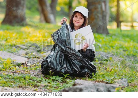 Close Of Photo Of A Pretty Young Girl Sitting On The Ground In The Park Holding A Paper With A Recyc