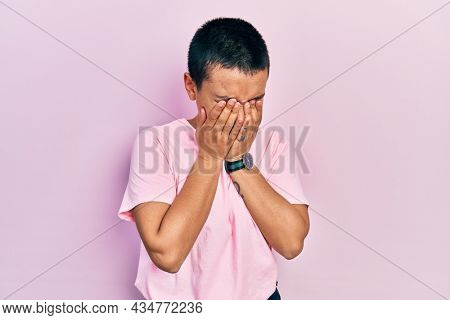 Beautiful hispanic woman with short hair wearing casual pink t shirt rubbing eyes for fatigue and headache, sleepy and tired expression. vision problem