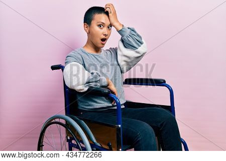 Beautiful hispanic woman with short hair sitting on wheelchair surprised with hand on head for mistake, remember error. forgot, bad memory concept.