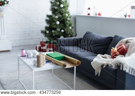 Couch With Warm Blanket And Gift Box Near Table With Twine, Decorative Ribbon And Wrapping Paper Nea