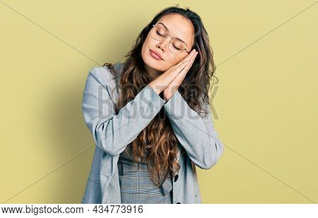 Young hispanic girl wearing business clothes and glasses sleeping tired dreaming and posing with hands together while smiling with closed eyes.