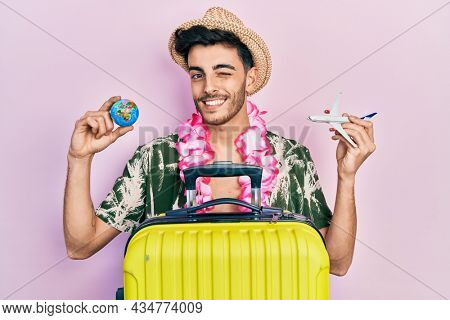 Young hispanic man wearing summer style and hawaiian lei holding world ball and plane toy winking looking at the camera with sexy expression, cheerful and happy face.