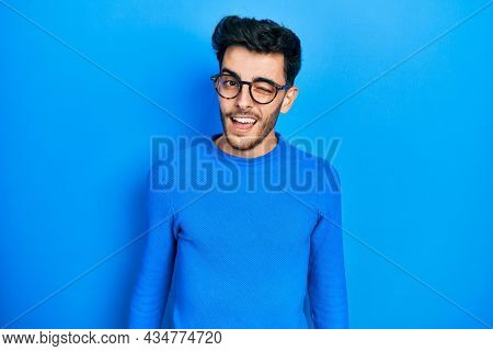 Young hispanic man wearing casual clothes and glasses winking looking at the camera with sexy expression, cheerful and happy face.
