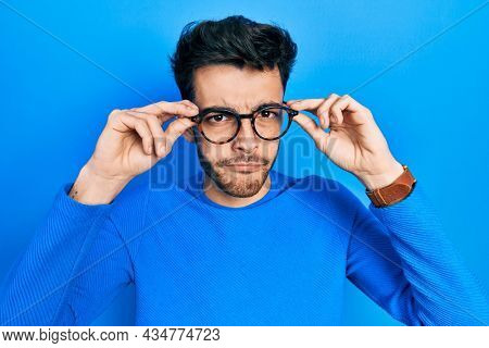Young hispanic man wearing glasses skeptic and nervous, frowning upset because of problem. negative person.
