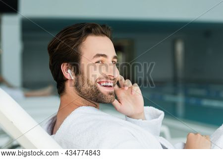 Smiling Man In Wireless Earphone And Bathrobe Relaxing On Deck Chair In Spa Center