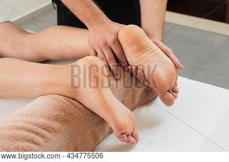 Cropped View Of Masseur Massaging Legs Of Man In Spa Center