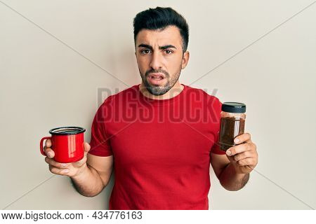 Young hispanic man holding cup of soluble coffee clueless and confused expression. doubt concept.