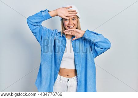 Beautiful blonde woman wearing wool hat smiling cheerful playing peek a boo with hands showing face. surprised and exited