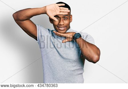 Young black man wearing casual t shirt smiling cheerful playing peek a boo with hands showing face. surprised and exited