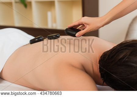 Cropped View Of Masseur Putting Hot Stone On Back Of Client In Spa Center