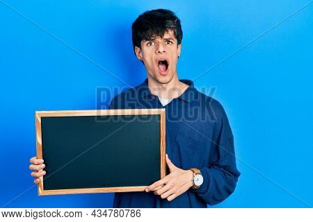 Handsome hipster young man holding blackboard in shock face, looking skeptical and sarcastic, surprised with open mouth