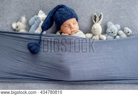 Adorable newborn baby boy wearing cute knitted hat sleeping under fabric with cute handmade toys. Infant child napping indoors