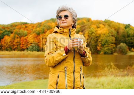 Portrait Of Attractive Senior Woman In Glasses Stands With Mug Hot Drink, Enjoys Autumn Against Of L