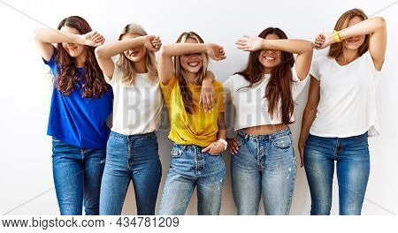 Group of young girl friends standing together over isolated background smiling cheerful playing peek a boo with hands showing face. surprised and exited