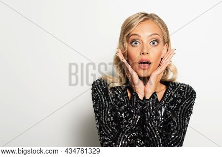 Astonished Woman In Black Blouse With Sequins Holding Hands Near Face While Looking At Camera On Whi