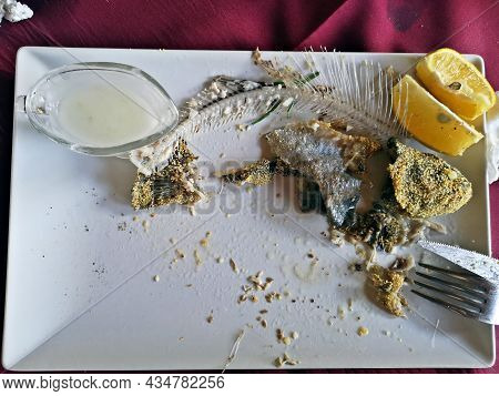 Food Scrap On A Plate At The Restaurant: Fish Bones And Skin, Lemon And Garlic Sauce.